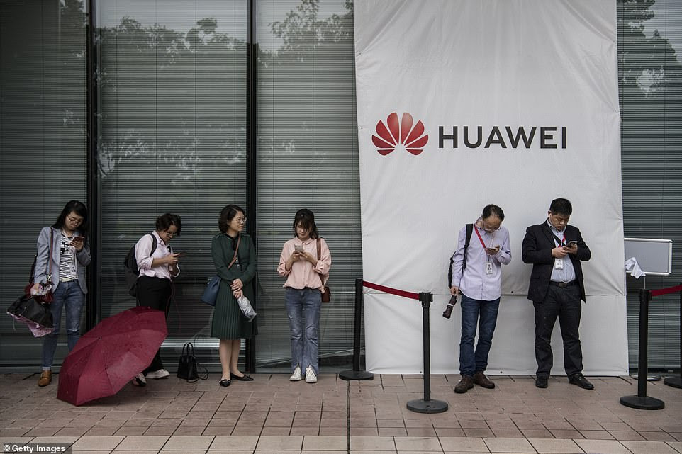 Huawei employees wait for a shuttle bus at the company's complex to take them back to Shenzhen city