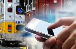 Person texting on smart phone with ambulance in background