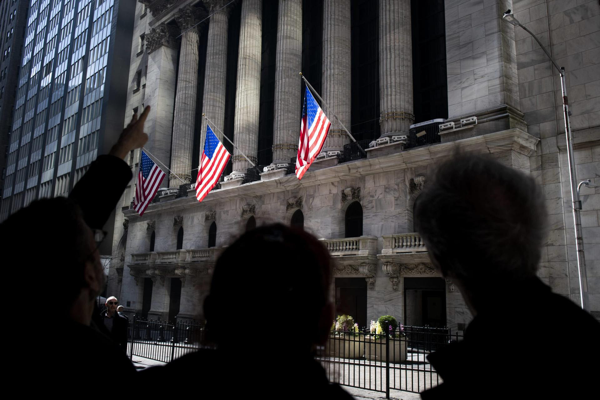 People pointing at Wall Street buildings