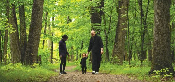 A family of three in the forest at Indian Springs Metropark, courtesy of Huron-Clinton Metroparks