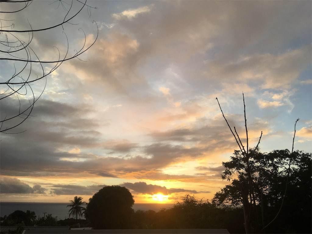 同じ視界の夕焼け。雲の間から夕陽の光が差し込む。