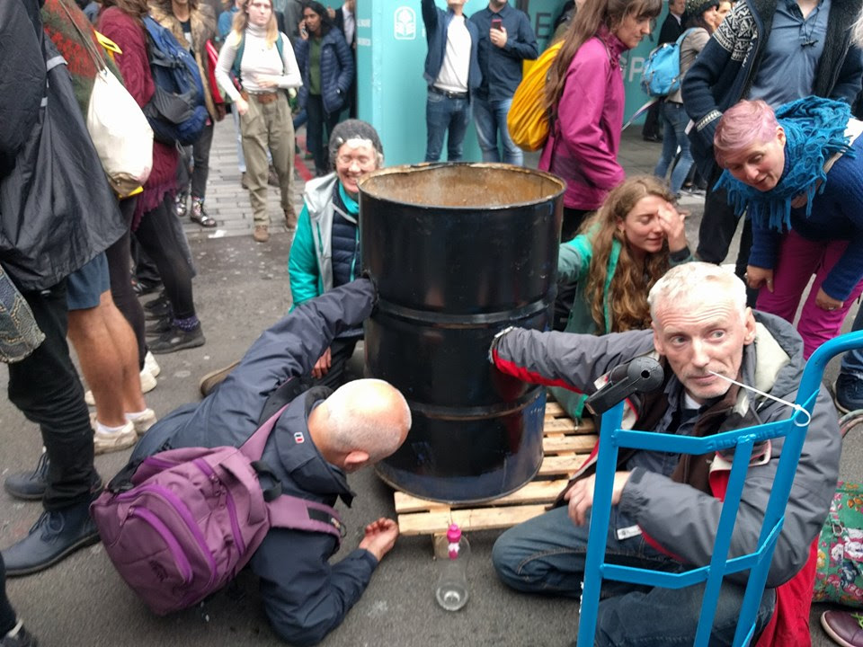 4 rebels blocking a road with an arm each locked into a black oil barrel.