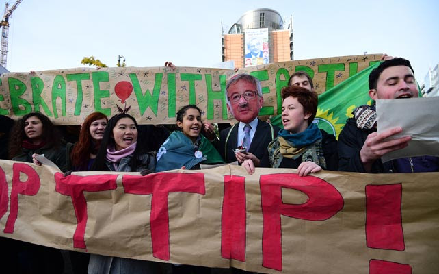 Activistas contra los tratados comerciales entre la UE y EEUU y Canadá (TTIP y CETA, respectivamente) posan junto a un Juncker ficticio frente a la sede de la Comisión Europea.