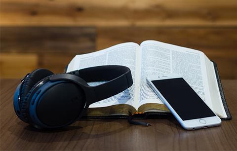 Headphones, a cellphone, and an open Bible