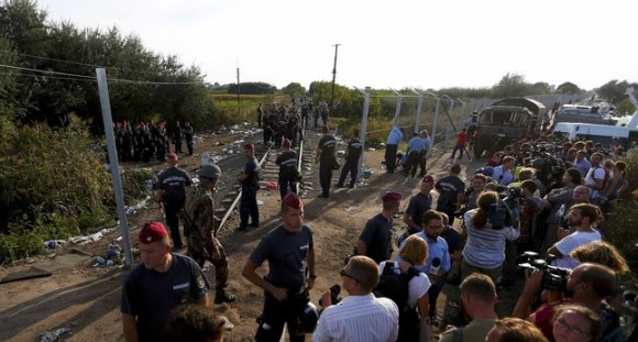 Journalists watch as Hungarian police officers seal off the border with Serbia, near the Hungarian migrant collection point in Roszke, Hungary, September 14, 2015, .  REUTERS/Laszlo Balogh