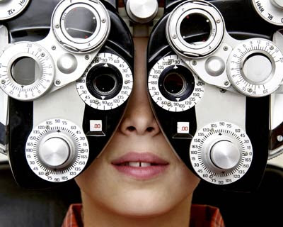 Photograph of a child looking through an eye exam instrument