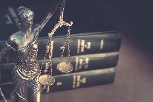 Estatuilla de la justicia y libros.