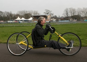 Picture of a person using an accessible bicycle to cycle around a park