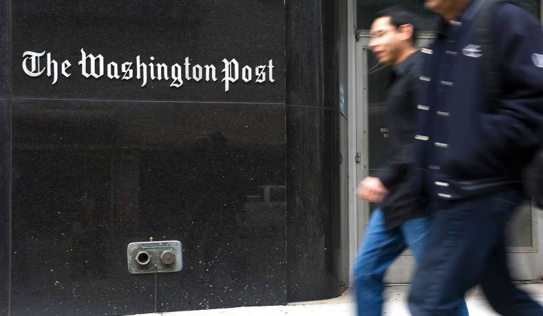 Two people walk briskly in front of The Washington Post building