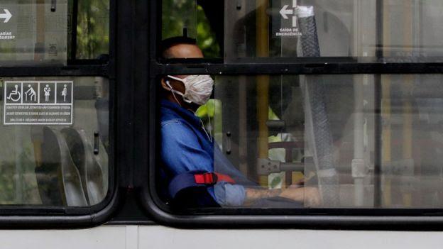 homem com máscara dentro de ônibus.