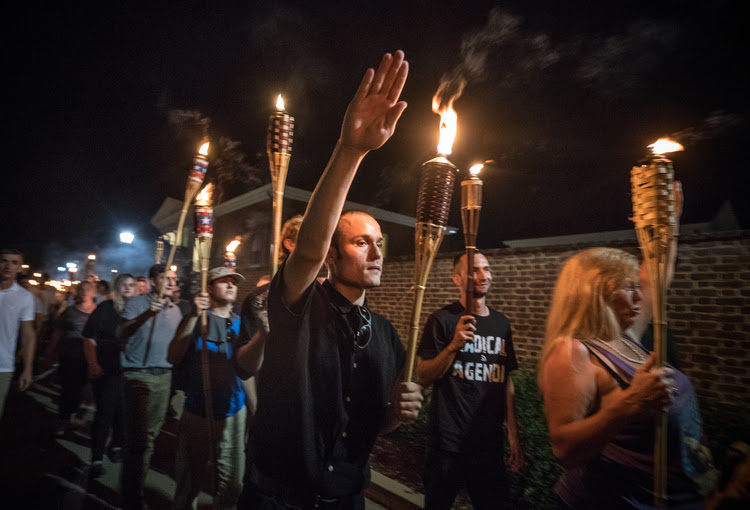 "White nationalists and white supremacists chant ""You will not replace us,"" ""Jews will not replace us,"" and ""white lives matter"" as they march through U-Va. (Evelyn Hockstein for The Washington Post)"