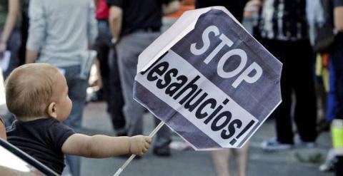 Niño portando una pancarta de 'Stop Desahucios'