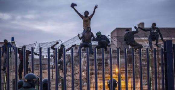 Inmigrantes subsaharianos encaramados a la valla de Melilla.- AFP