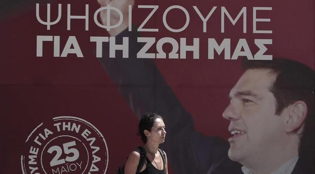 Una mujer pasa por delante de un cartel elecotral de SYRIZA en el centro de Atenas, Grecia.