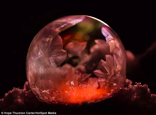 Inner glow: A                                                    mysterious-looking red                                                    light shines from                                                    within this bubble of                                                    frozen soapy water