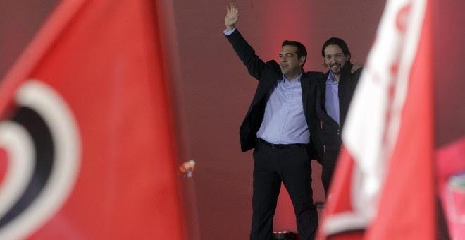 El líder del partido español Podemos, Pablo Iglesias, saluda acompañado por el líder de Syriza, Alexis Tsipras. EFE/Yannis Kolesidis