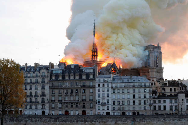 Slide 26 of 31: Seen from across the Seine River, smoke and flames rise during a fire at the landmark Notre-Dame Cathedral in central Paris on April 15, 2019, potentially involving renovation works being carried out at the site, the fire service said. (Photo by FRANCOIS GUILLOT / AFP)        (Photo credit should read FRANCOIS GUILLOT/AFP/Getty Images)