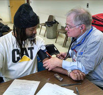 MRC volunteer checks patient's blood pressure at a clinic