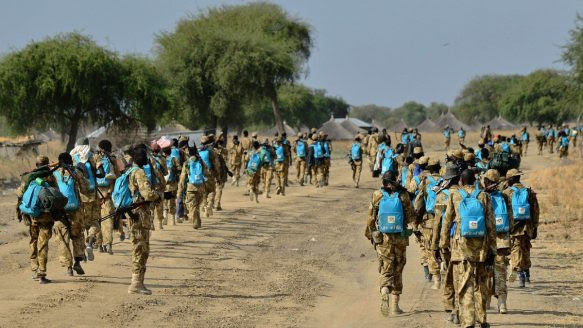 Sudan People's Liberation Army (SPLA) soldiers wearing UNICEF backpacks walk along a road in Mathiang near Bor on Jan. 31, 2014.