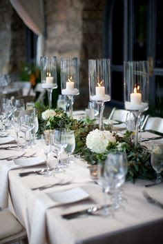 Outdoor reception table with long-stemmed hurricane candle holders and table runner made of olive leaves