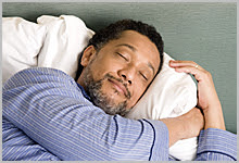 Man peacefully sleeping with a smile on his face.
