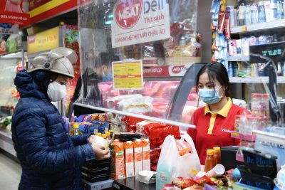 A customer pays in a corner shop where a plastic divider is installed as a measure against the spread of the coronavirus disease (COVID-19) at a shop in Hanoi, Vietnam, 18 February, 2021 (Photo: Reuters/Thanh Hue).