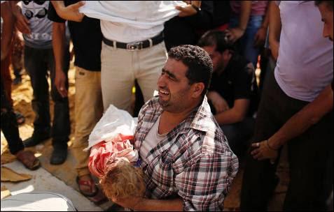 Un familiar sostiene el cadáver de una niños palestino, asesinado junto con su padre y otros seis miembros de la misma familia por un tanque israelí, antes de su entierro durante su funeral en Beit Lahiya, en el norte de la Franja de Gaza.