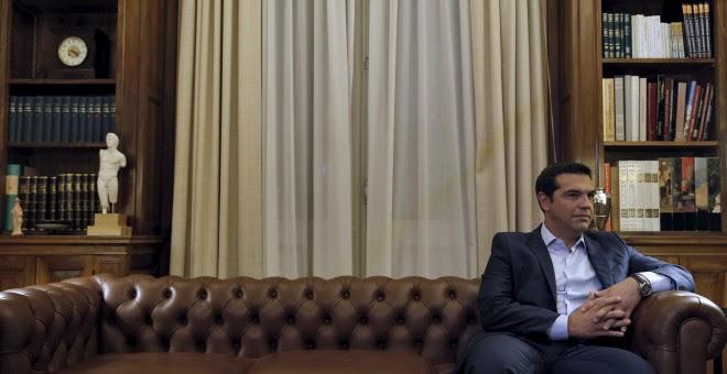 El primer ministro griego Tsipras, sentado en un sofá antes de comunicar al jefe de Estado su dimisión, en Atenas (Grecia). REUTERS