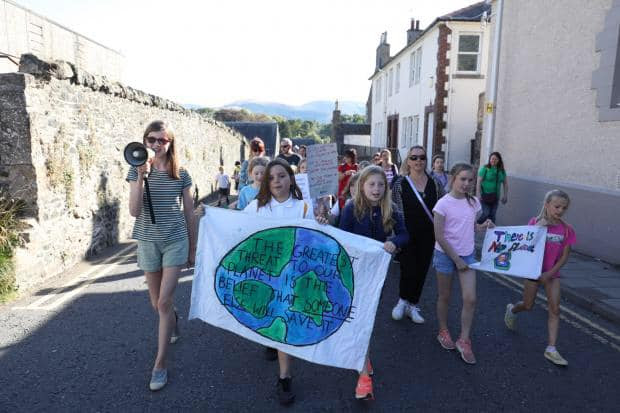A group of around 20 schoolchildren marching up a street, one is holding a megaphone and two others are holding a sign which reads 'The greatest threat to our planet is the belief that someone else will save it'.