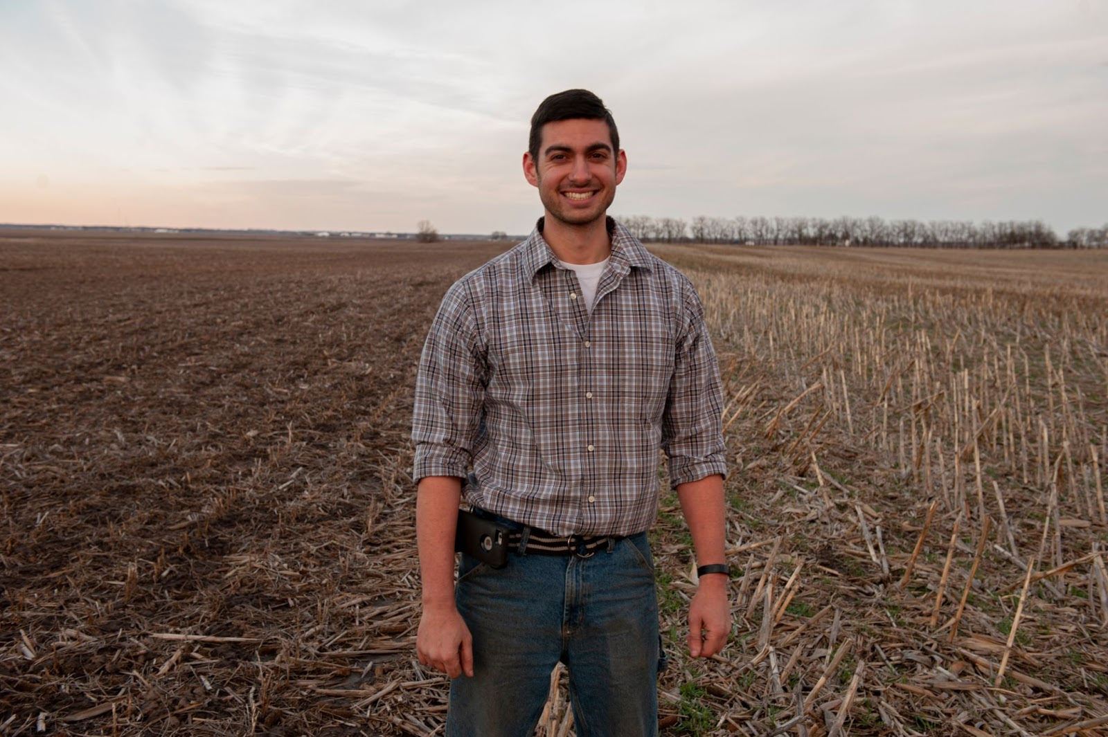 Image of Frank Rademacher standing and smiling on the dividing line between his field of cover crops and his neighbors bare soil.