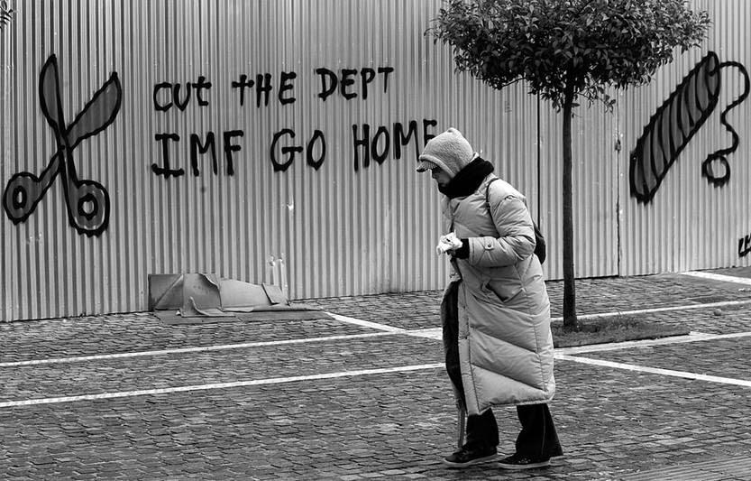 """Un grafiti en el que se lee """"Rebaja la deuda. FMI, vete a casa"""" es visto ayer, en una valla de la Academia de las Ciencias de Atenas (Grecia). Foto: Orestis Panagiotou, Efe"""