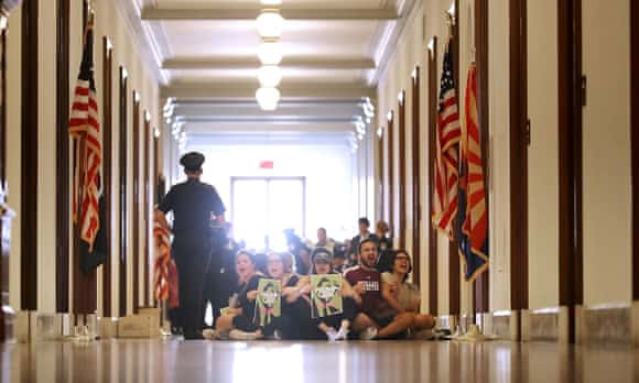 Demonstrators from Arizona chant 'kill the bill or lose your job' while sitting on the floor outside the office of Senator Jeff Flake.