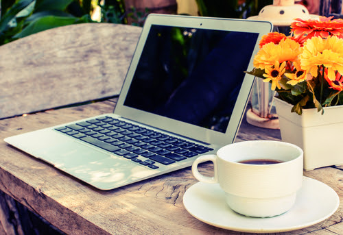 a cup of coffee and laptop on wood floor with flower_ vintage style