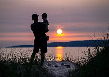 man standing on dune holding child