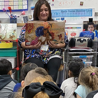 kindergarten teacher Gloria Pereyra-Robertson reads to students