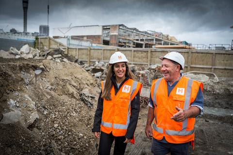 A man and a woman in high-visibility vests and helmets walk through a construction site