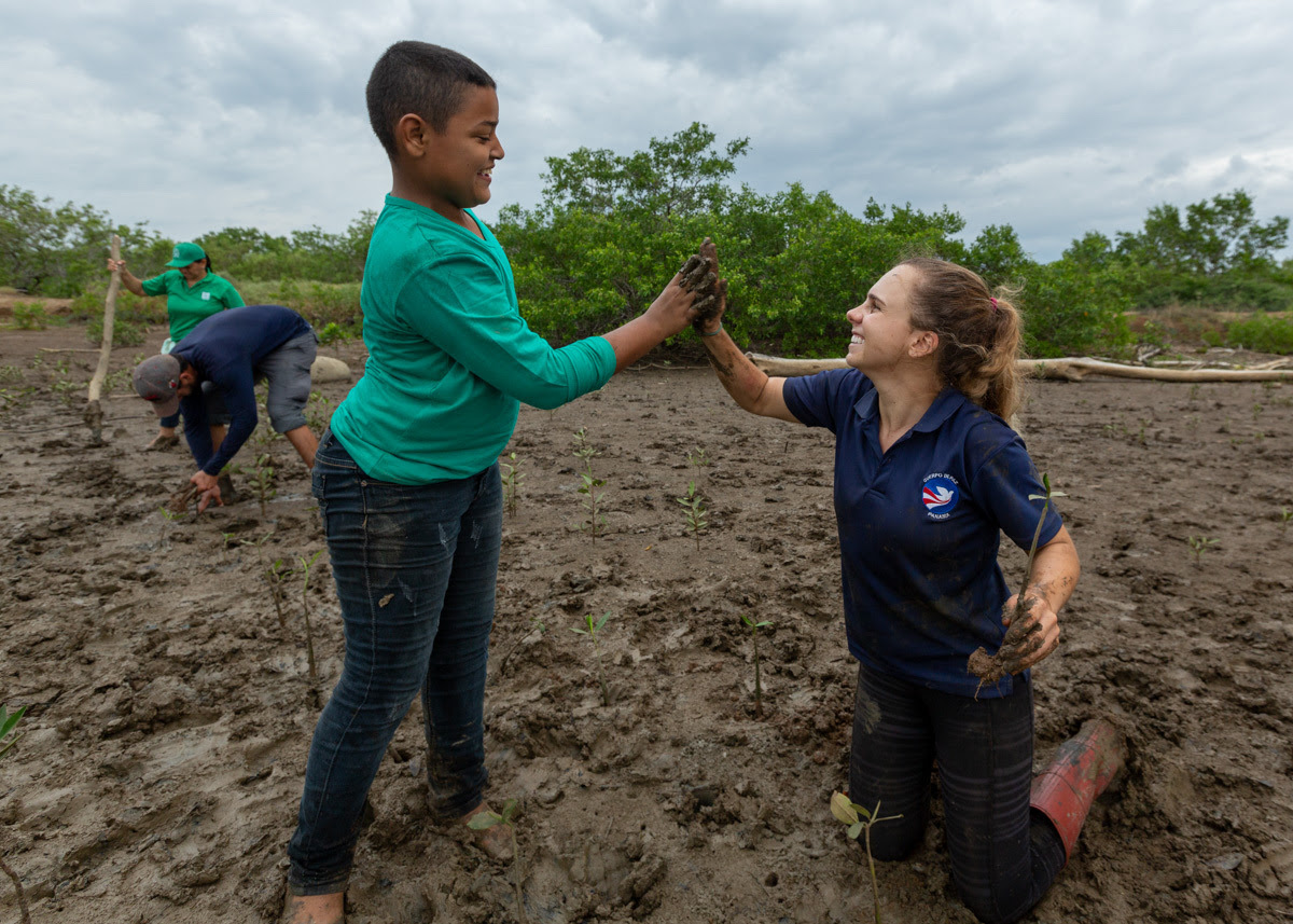 Peace Corps Volunteer high fives Panamanian Child as they work on planting trees