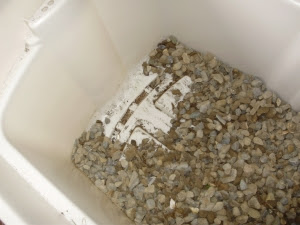 Bin showing drainage holes in one end, with 5cm gravel then spread on base.