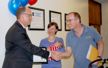 Clerk of the Board David Hall congratulates the family of the 200,000th passport.