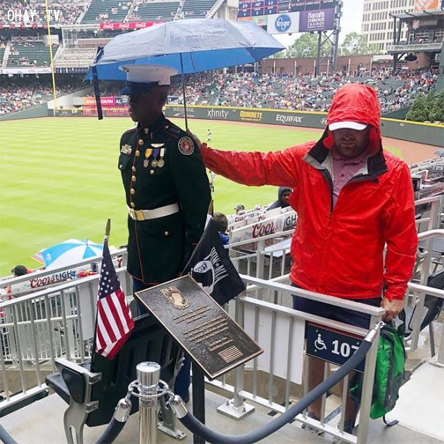 Fan bóng chày cầm ô che cho sĩ quan dự bị trong Ngày Tưởng niệm Liệt sĩ ở Mỹ.,Hoa Kỳ,nước mỹ,lòng nhân ái
