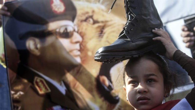 A supporter of Egypt's President Abdel Fattah el-Sisi holds a military boot on her head in a sign of support for military rule in 2014 [AFP]