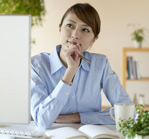 woman pondering while sitting at a computer