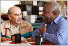 Two senior men having coffee.