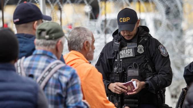 Um oficial de fronteira verifica um passaporte no cruzamento da fronteira entre Tijuana e os EUA.