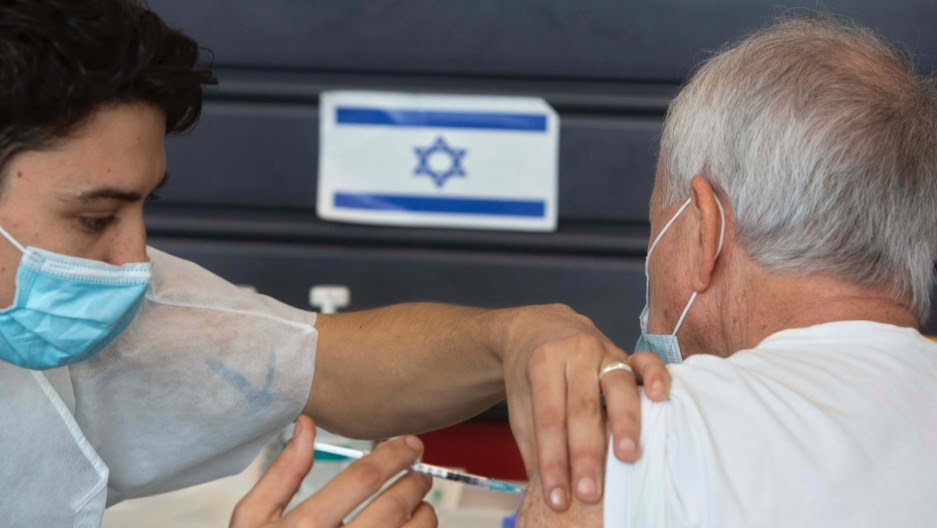 An Israeli receives a coronavirus vaccine from medical staff at a COVID-19 vaccination center in Tel Aviv, Israel, Jan. 6, 2021.