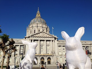Two large inflated white rabbit sculptures appear in the foreground_ in front of a large ornate civic building with a dome on top. Behind is a deep blue sky.