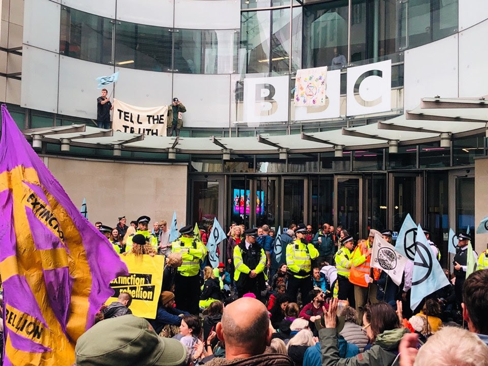 An XR demonstration in front of the BBC building in London. Some rebels are sat on the floor in front of the entrance, where a line of police officers stand behind them. Two (Scottish!) rebels are on the roof of the entrance doors with a sign that reads 'TELL THE TRUTH'.