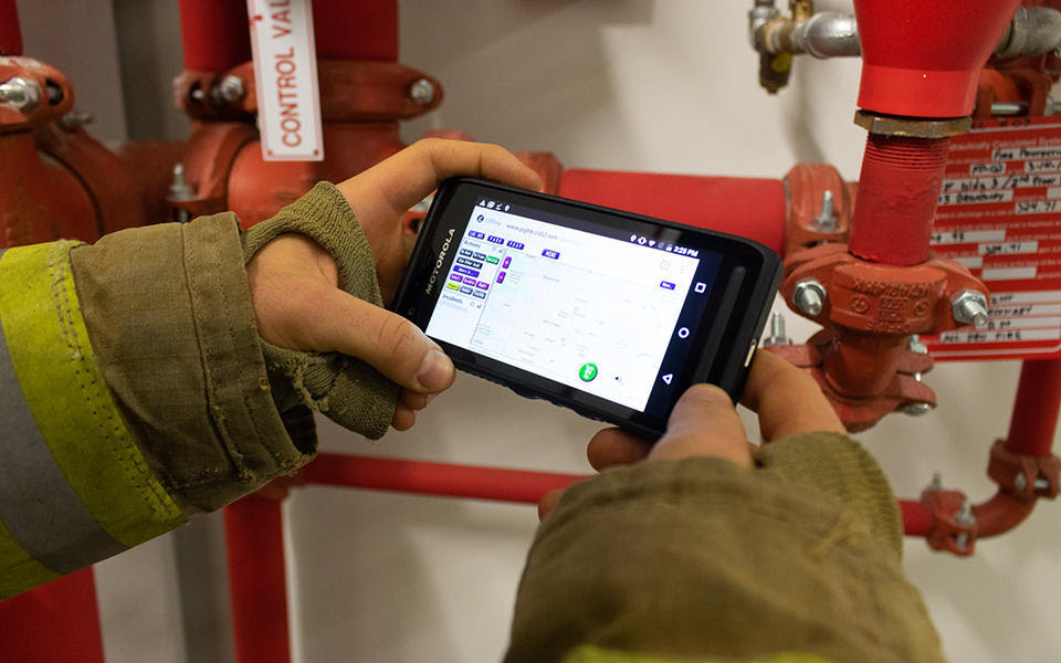 A person wearing a firefighter's coat holds a smartphone.