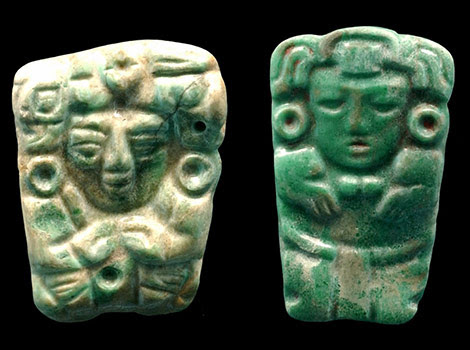 Intricate jade pendants with carved faces and bodies