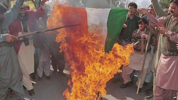 A group of pro-Kashmir supporters give a cheer as the Indian national flag is burnt during a small rally to observe solidarity day near the Indian High Commission in Islamabad, Saturday, Feb. 5, 2000.